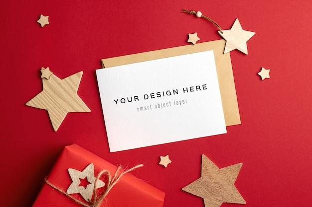 Mockup di biglietto di auguri di natale con scatole regalo e decorazioni in legno sul rosso Psd Premium