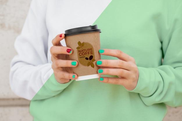 Femmina del primo piano con il caffè bevente di maglia con cappuccio Psd Premium