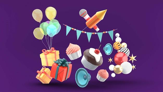 Cupcakes circondati da scatole regalo, palloncini, altoparlanti, bandiere a forma di spago e schiacciati su un viola Psd Premium