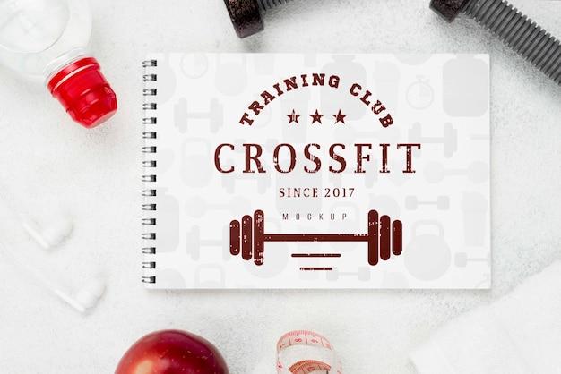 Lay piatto di notebook fitness con pesi e mela Psd Premium