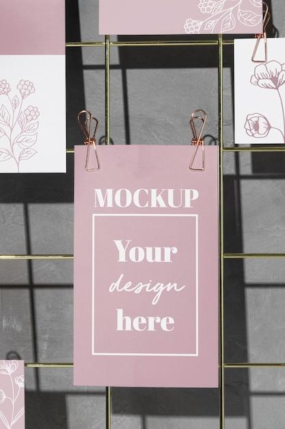 Cartoline floreali appese su una griglia metallica con clip rosa Psd Premium