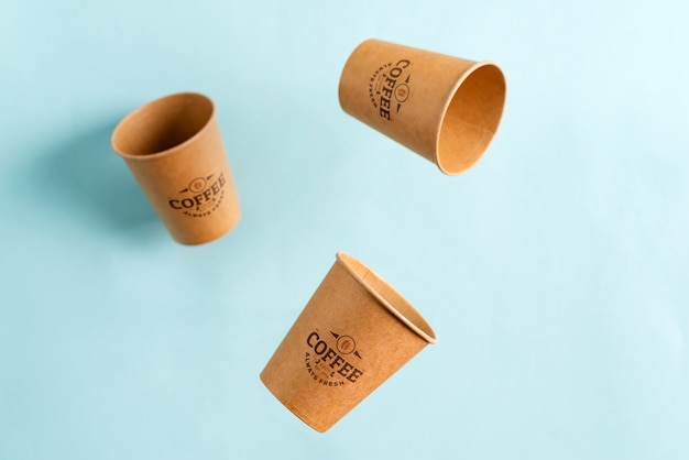 Tazze eliminabili volanti del modello della carta amichevole di eco sopra fondo blu pastello. rifiuti zero Psd Premium