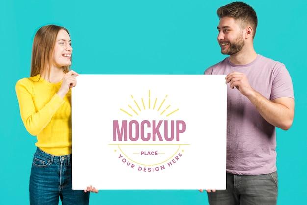 Amici che tengono una carta mock-up di cancelleria Psd Premium