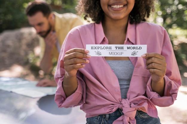 Vista frontale della donna sorridente in campeggio e in possesso di un pezzo di carta Psd Premium