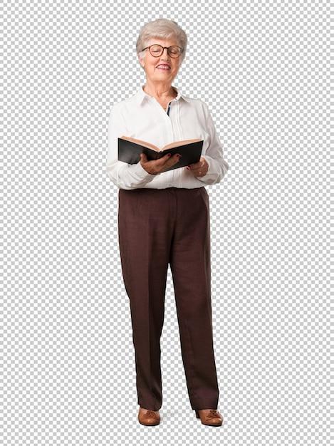 Full body senior woman concentrato e sorridente, con in mano un libro di testo, studiando per superare un esame o leggere un libro interessante Psd Premium