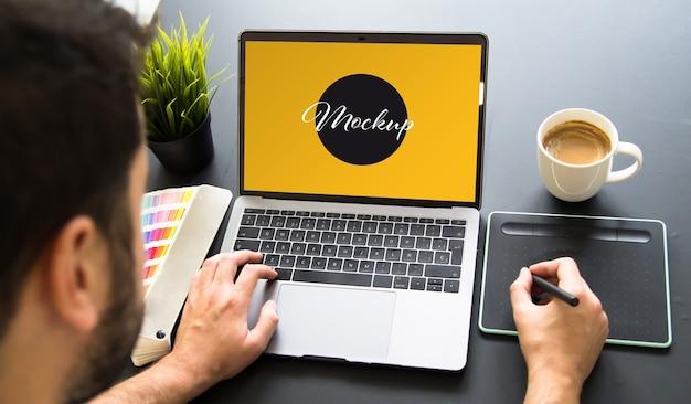 Graphic designer che lavora al mockup del laptop Psd Premium
