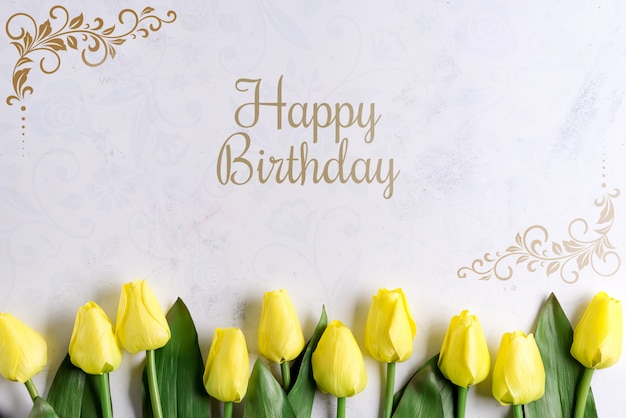 Il tulipano giallo di buon compleanno fiorisce su fondo di pietra, disposizione piana con lo spazio della copia Psd Premium