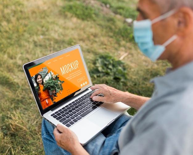 Elevato angolo di uomo sul computer portatile nel parco Psd Premium