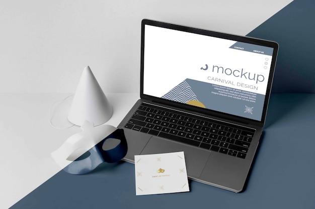 Alto angolo di invito di carnevale minimalista con laptop e maschera Psd Premium