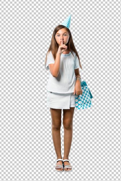 Bambina a una festa di compleanno in possesso di un sacchetto regalo mostrando un segno di chiusura della bocca Psd Premium