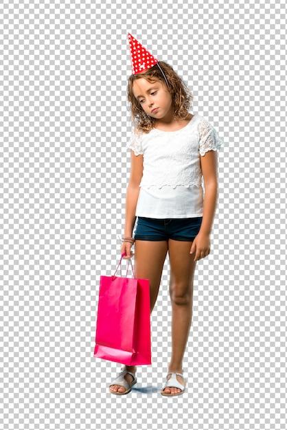 Bambina ad una festa di compleanno che tiene un sacchetto del regalo infelice e frustrato con qualcosa Psd Premium