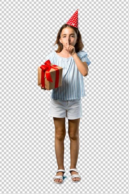 Bambina ad una festa di compleanno in possesso di un regalo che mostra un segno di chiusura bocca e gesto di silenzio Psd Premium