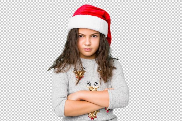 La bambina che celebra il giorno di natale che aggrotta le sopracciglia nel dispiacere, tiene le braccia conserte. Psd Premium