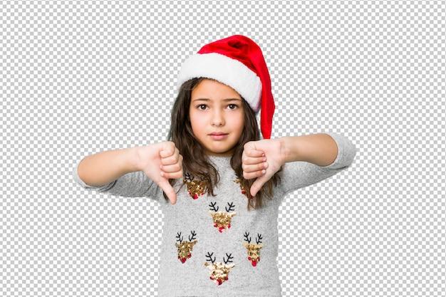 Bambina che celebra il giorno di natale che mostra pollice giù e che esprime antipatia. Psd Premium