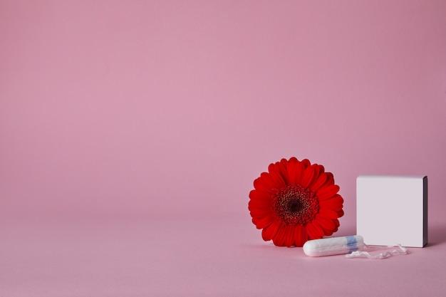 Tamponi mestruali e fiore rosso isolati sulla tavola rosa, vista superiore. copia spazio Psd Premium