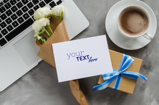 Manichino di biglietto di auguri con computer portatile, confezione regalo, caffè del mattino e fiori. Psd Premium