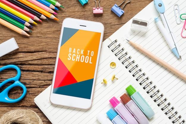 Derida sul telefono cellulare con gli oggetti stazionari della scuola su legno di lerciume Psd Premium