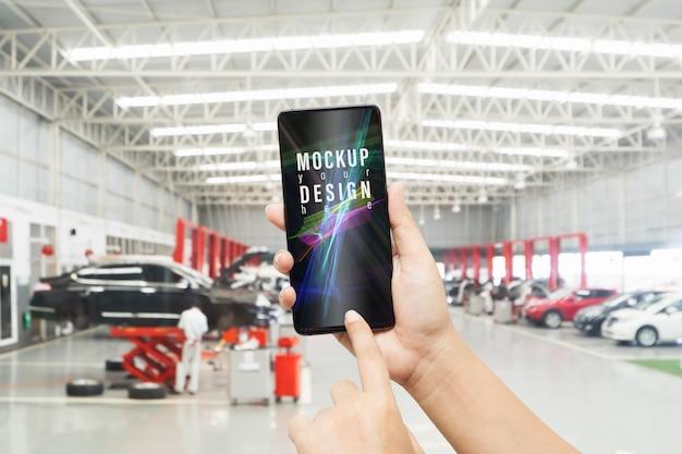 Smartphone del modello nell'officina riparazioni dell'automobile. Psd Premium