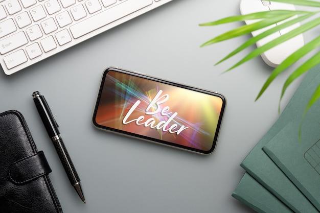 Smartphone del modello sulla scrivania funzionante. Psd Premium