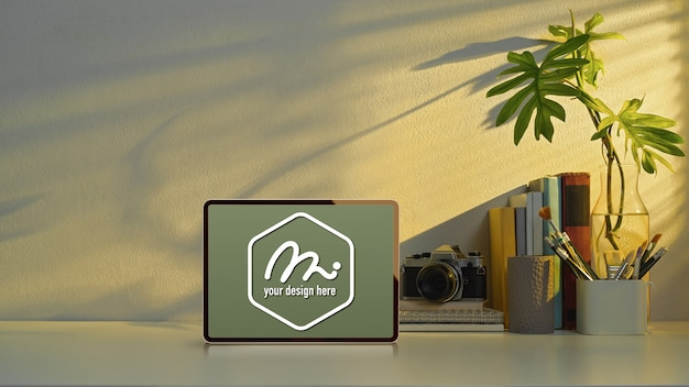 Mockup tablet sul tavolo di studio con copia spazio, fotocamera e elementi di scuola in ufficio a casa Psd Premium