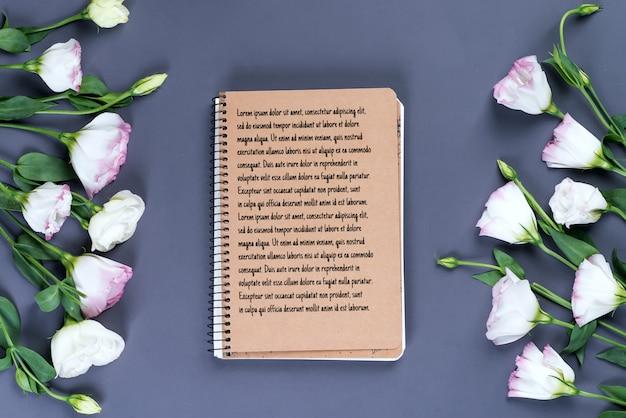 Apra il taccuino e il mazzo vuoti del eustoma dei fiori sul modello di carta scuro Psd Premium