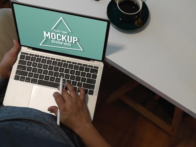 Scatto dall'alto di impiegato maschio che lavora con mock up laptop Psd Premium