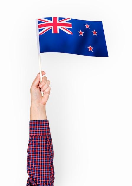 Persona che sventola la bandiera della nuova zelanda Psd Premium