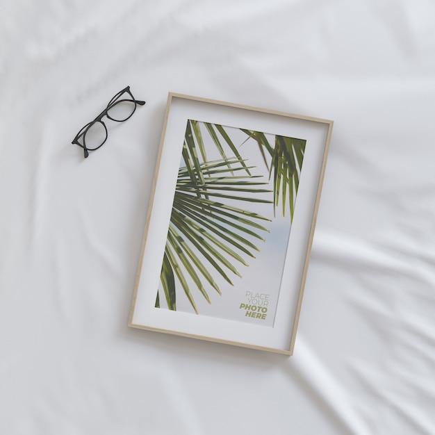 Mockup di cornice con gli occhiali sul letto Psd Premium