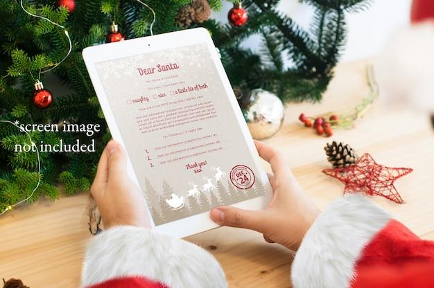 Santa che legge una lettera digitale sul modello di tablet Psd Premium