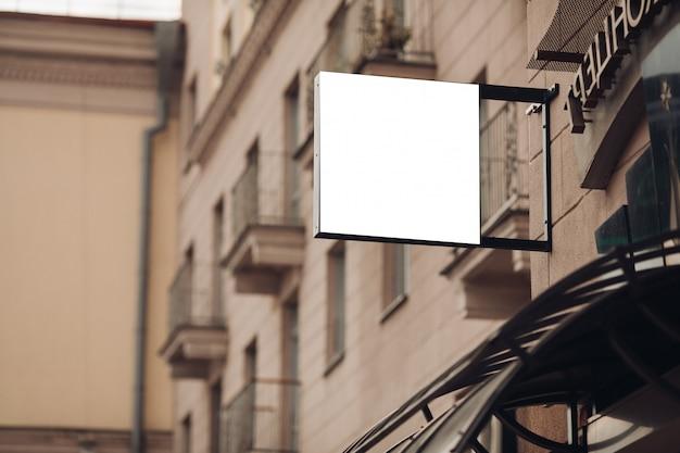 Un piccolo tabellone per le affissioni, modello su un edificio nel centro della città con una pubblicità di caffè Psd Premium