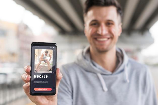Uomo di smiley che tiene smartphone mentre si lavora fuori all'aperto Psd Premium