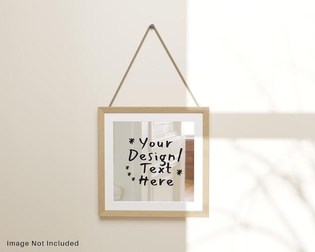 Specchio quadrato a riflessione con cornice in legno appesa al modello a parete Psd Premium