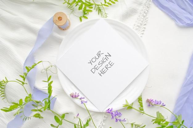 Cartolina d'auguri del modello della cancelleria di estate o invito di nozze con i fiori viola e i nastri di seta delicati su uno spazio bianco Psd Premium