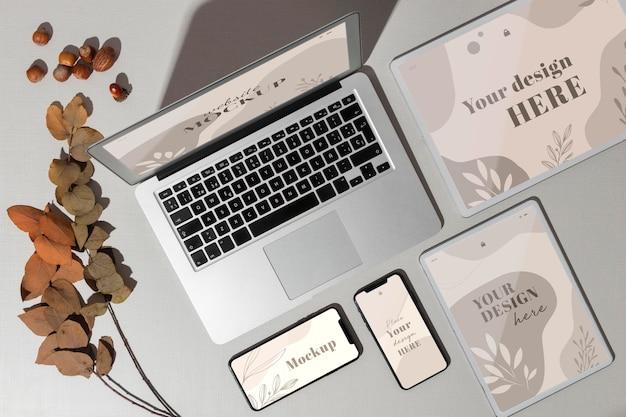Dispositivi con vista dall'alto con mockup accanto alle foglie Psd Premium