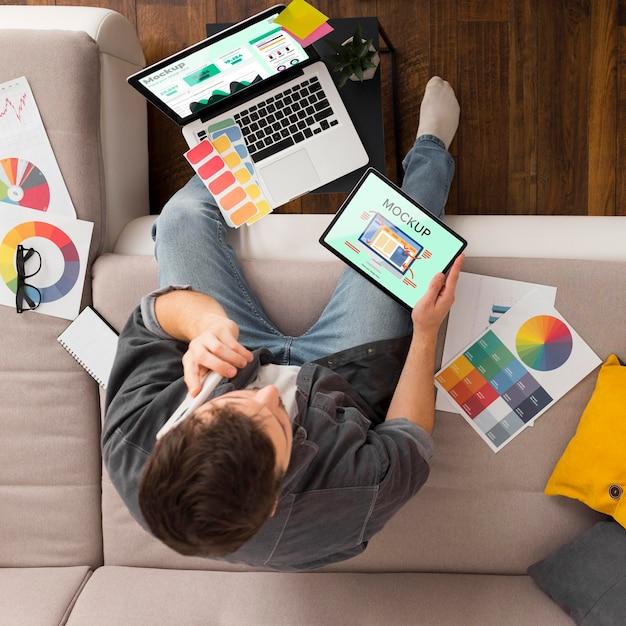 Uomo di vista dall'alto sul divano con tablet e laptop mock-up Psd Premium