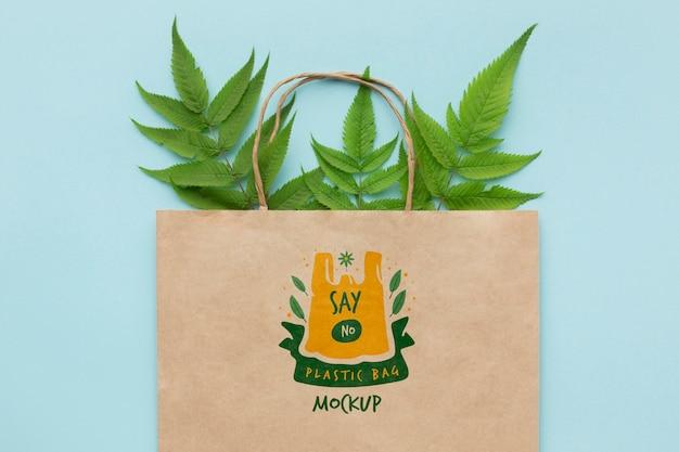 Mock-up di sacchetto di carta vista dall'alto con foglie Psd Premium