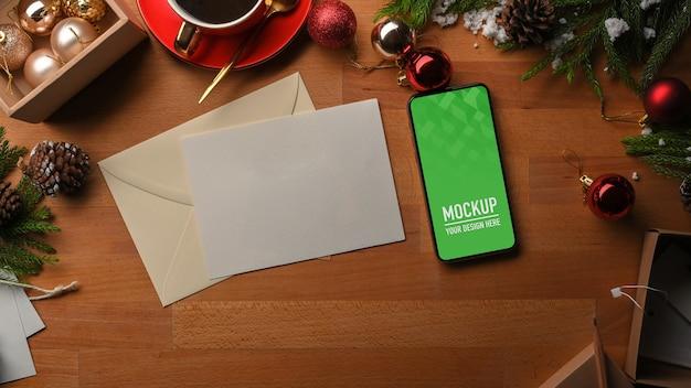 Vista dall'alto del mockup dello smartphone e delle decorazioni natalizie Psd Premium