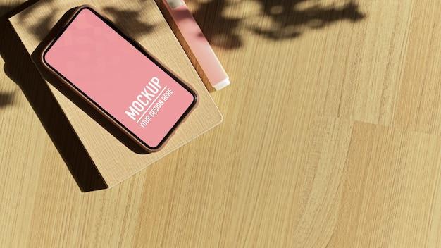 Vista dall'alto del tavolo in legno con mockup di smartphone Psd Premium