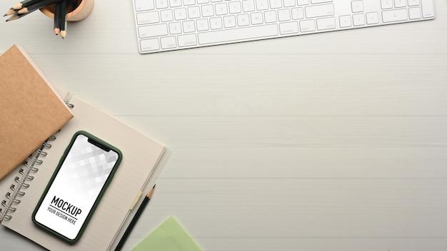 Vista dall'alto dell'area di lavoro con il mockup dello smartphone Psd Premium