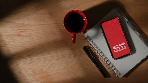 Vista dall'alto del piano di lavoro con mockup di smartphone, taccuino, penna e tazza di caffè Psd Premium