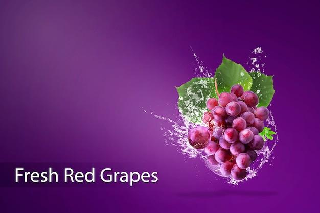 Innaffi la spruzzatura sull'uva rossa fresca sopra fondo rosso. Psd Premium