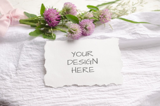 Mockup di nozze con bordi frastagliati con fiori rosa e delicati nastri di seta su uno sfondo bianco. Psd Premium