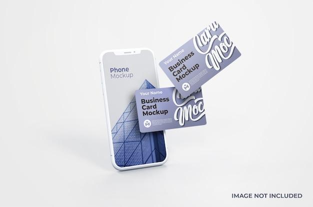 Smartphone bianco con mockup di biglietti da visita Psd Premium