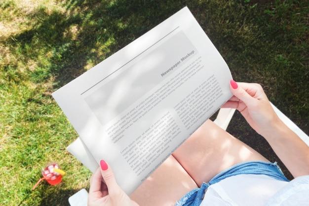 Donna che legge il giornale nel mockup del cortile Psd Premium