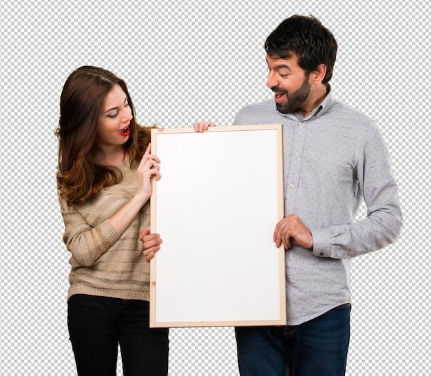 Giovani coppie che tengono un cartello vuoto Psd Premium