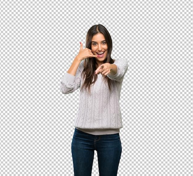 Giovane donna ispanica del brunette che fa gesto del telefono e che indica fronte Psd Premium
