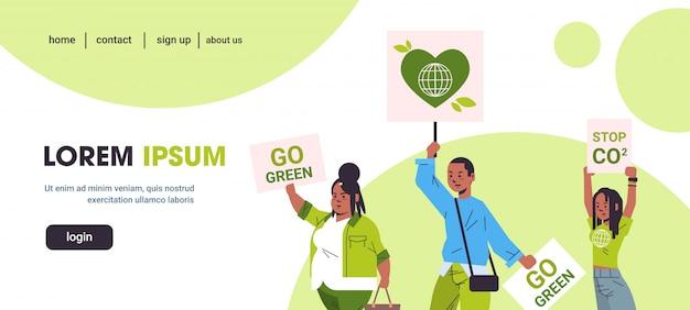 Attivisti in possesso di manifesti andare green stop co2 salvare pianeta sciopero concetto manifestanti afro-americani che fanno una campagna per proteggere la terra dimostrando contro il riscaldamento globale ritratto orizzontale Vettore Premium