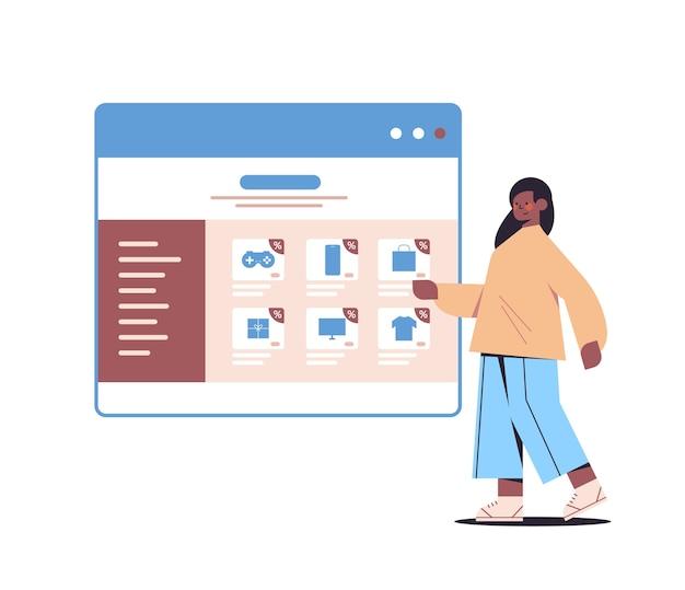 Donna afro-americana che sceglie gli acquisti nella finestra del browser web shopping online cyber lunedì vendita sconti vacanze concetto di e-commerce Vettore Premium