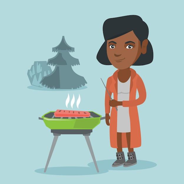 Donna africana che cucina bistecca sul barbecue. Vettore Premium