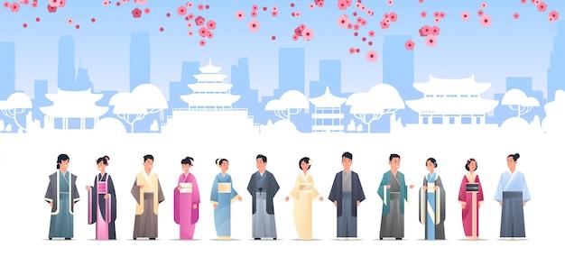 Gruppo di persone asiatiche in abiti tradizionali uomini donne che indossano costumi antichi in piedi insieme caratteri cinesi o giapponesi su edifici pagoda paesaggio Vettore Premium